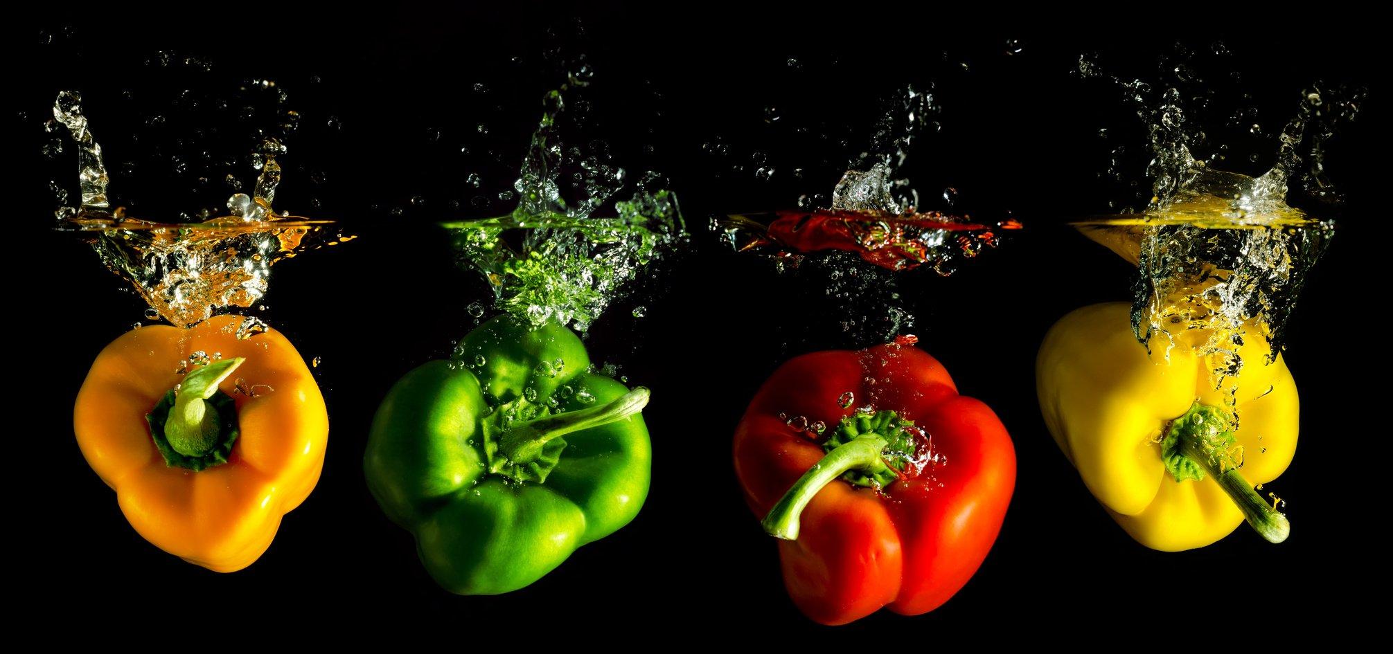 Food Intolerance vier verschieden farbige Paprika fallen ins Wasser