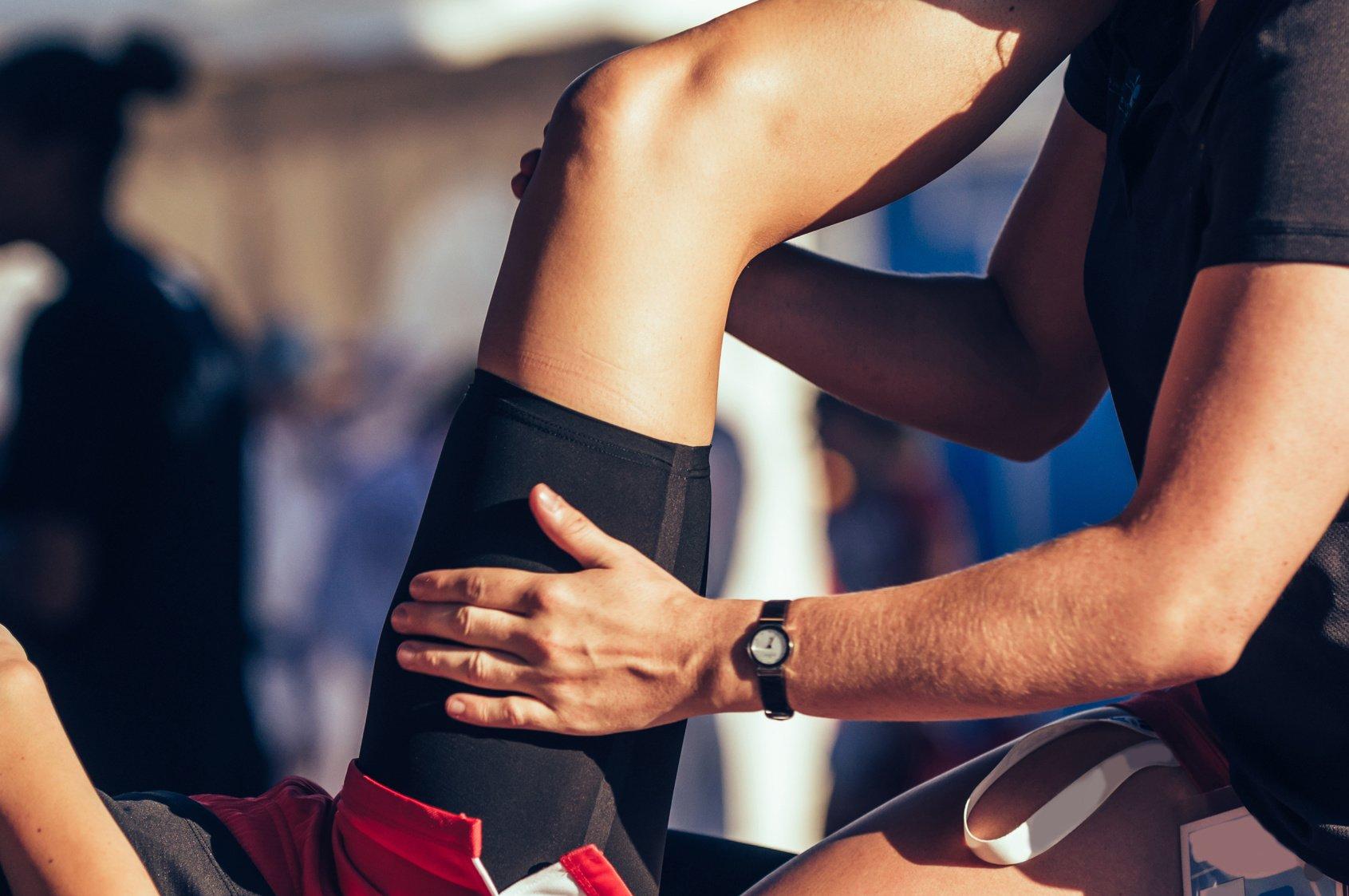 Sport therapist massaging leg of an athlete