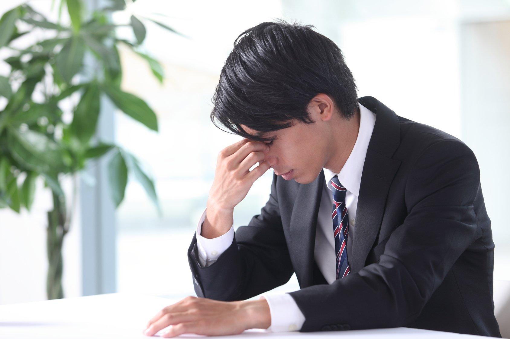 Headaches business man holding head