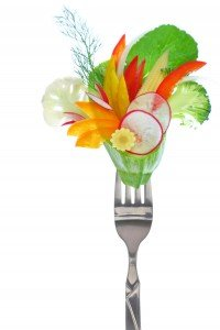 Detoxification Fresh colorful vegetables on fork, isolated on white