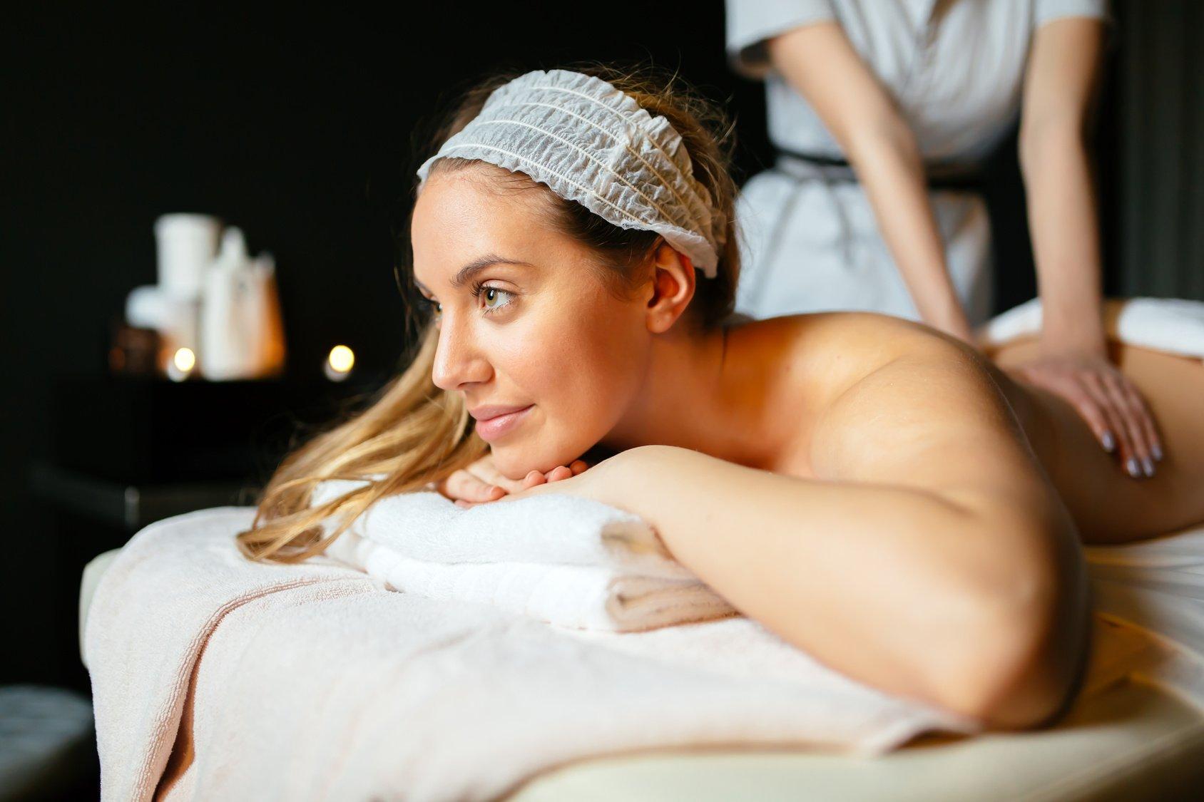 Lovely brunette enjoying massage treatment by therapist