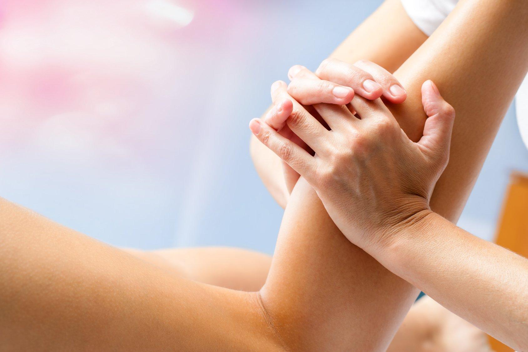 Macro close up of osteopath massaging female calf muscle. Hands manipulating lower leg muscle.